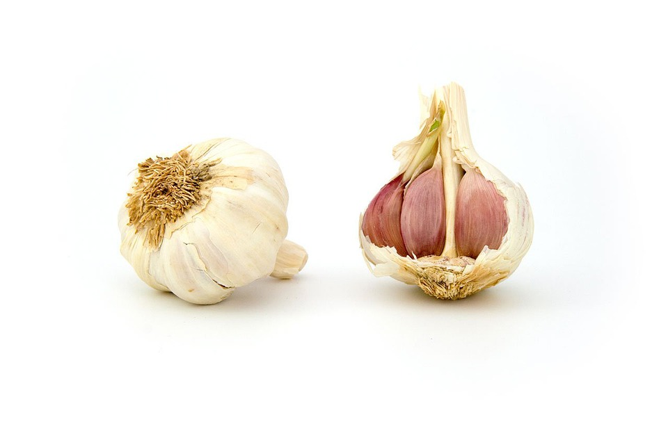 Peeled and unpeeled garlic sitting side by side on a table