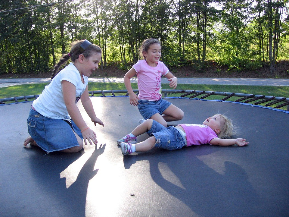 three female kids on a trampoline