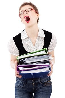 A secretary with mouth open wide in a sign and carrying lot of files to signify being overwhelmed