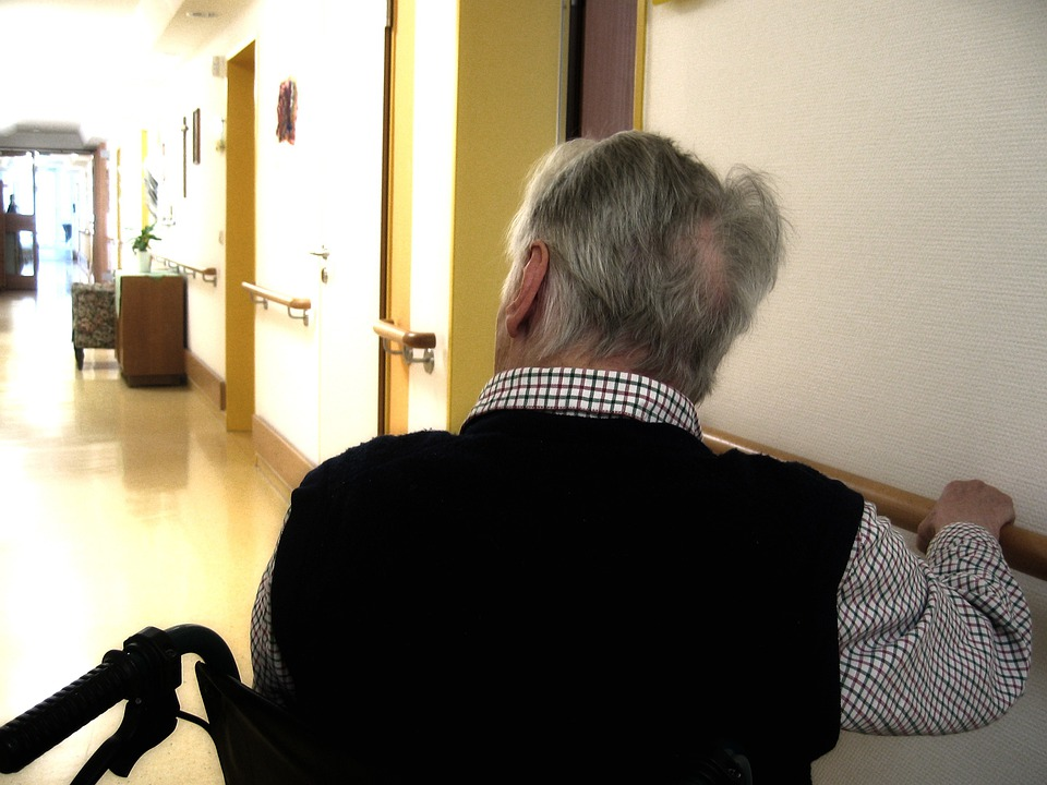 Old man sitting on the wheelchair has a dementia