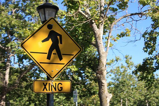 A road sign with a man crossing a street and under it the name XING, both black on yellow backgrounds
