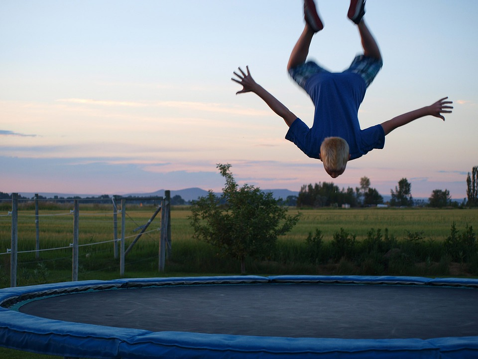 boy in blue shirt jumping on the round blue trampoline