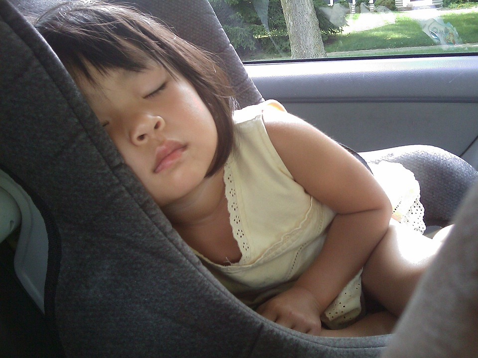 baby girl sleeping on a car seat