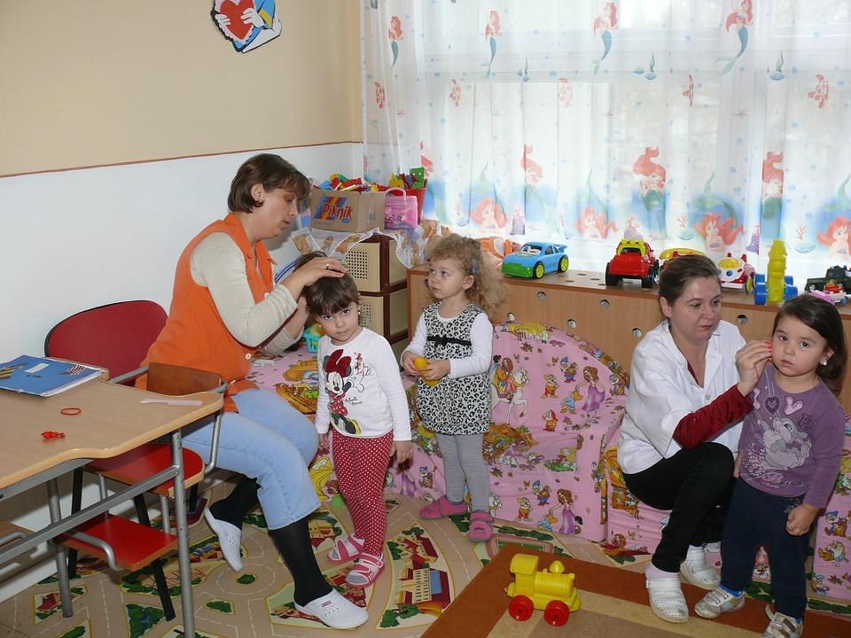 2 professoras prendem os cabelos de 2 crianças em sala de aula. Uma terceira criança está em pé olhando para a professora.