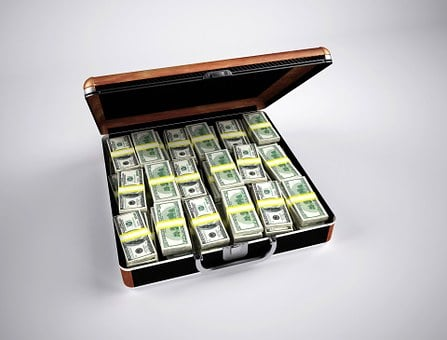 Wads of dollar bills stuffed into a briefcase