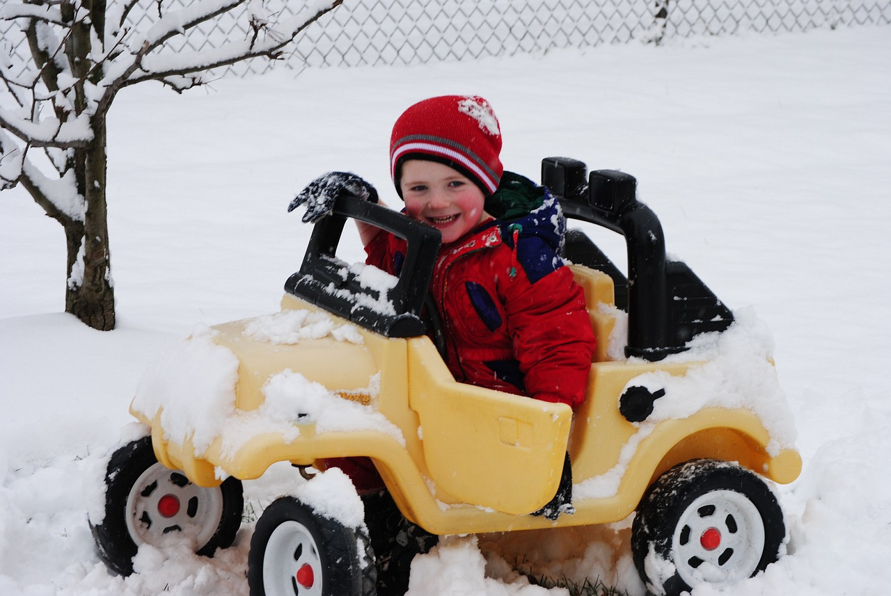 Child in play car in the snow