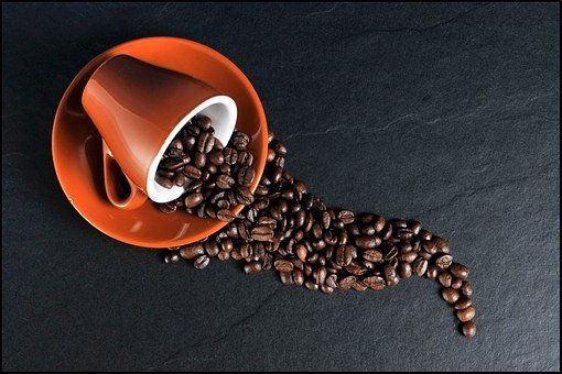 coffee beans on orange ceramic mug