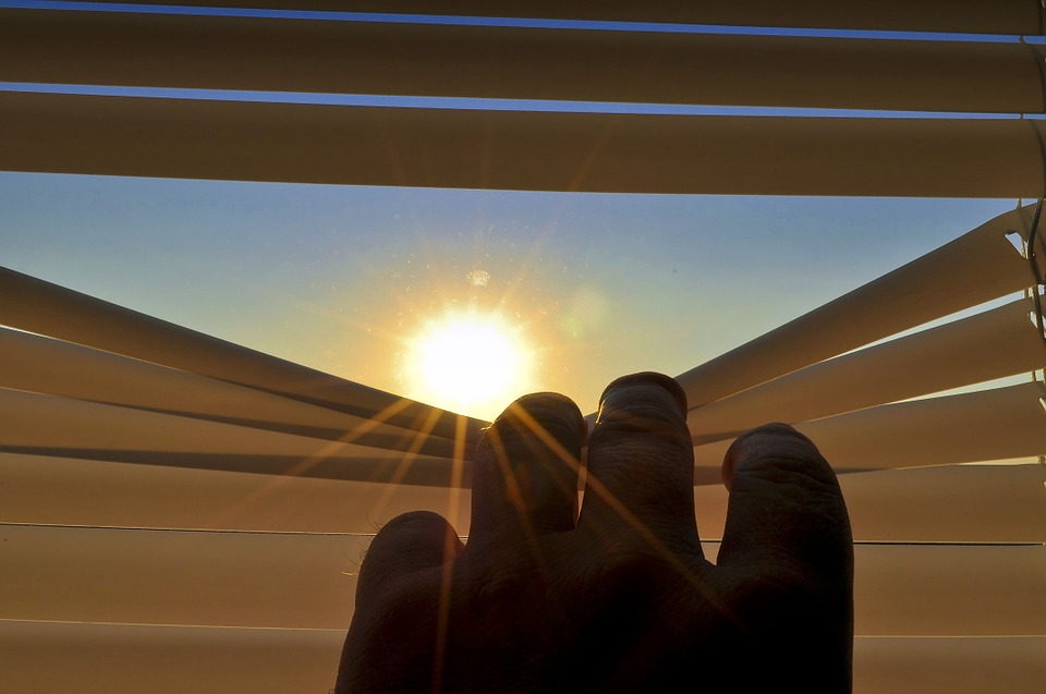 Photo of a person pulling down roller blinds to see the sun