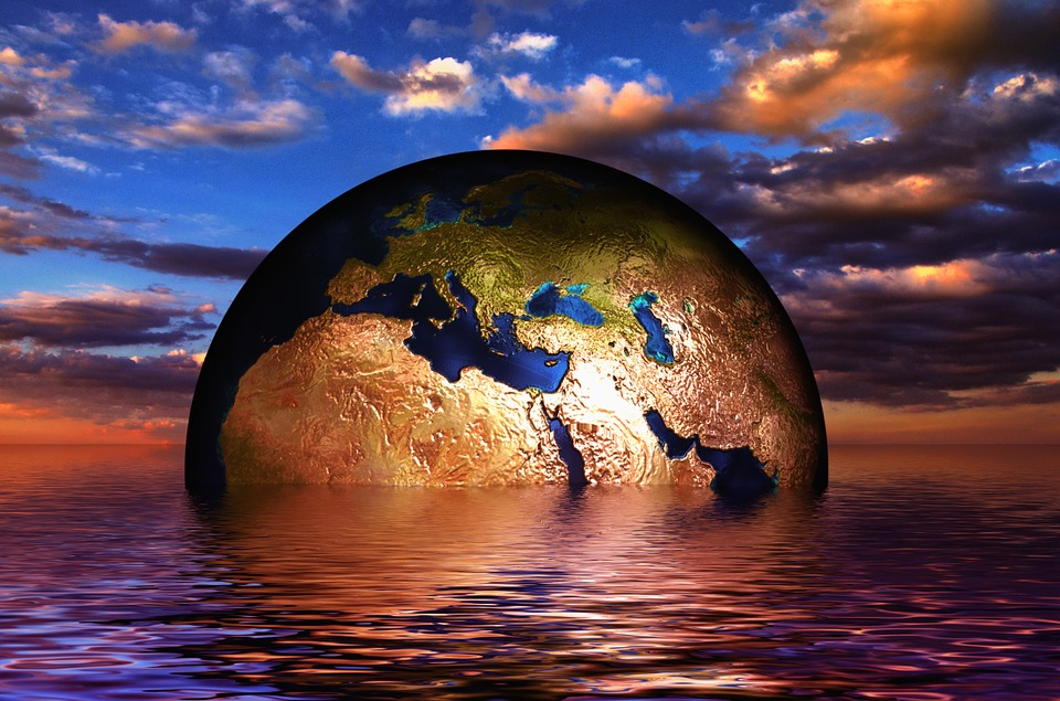 ID: skyscape over a body of water. The body of water holds a globe that resembles earth, the continents Africa and Asia are facing the viewer. The globe is partly submerged up to the southern 3/4s of Africa and the southern 1/4 of the Arabian Peninsula.