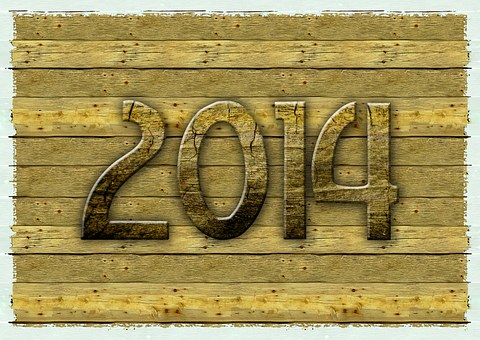 The year 2014 written in embossed letters on a yellowish wooden background