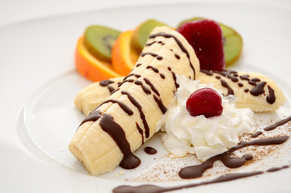sliced of bananas kiwi orange strawberry and cherry with chocolate syrup