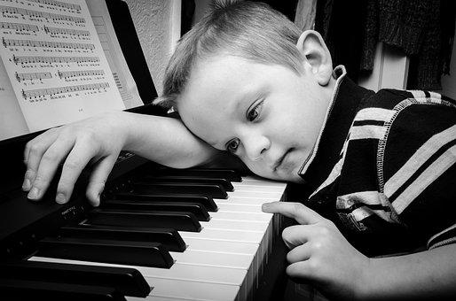Boy lying down on a piano