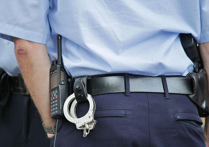 Rear view of a police officer showing his cuffs and radio.   Photo: Pixabay