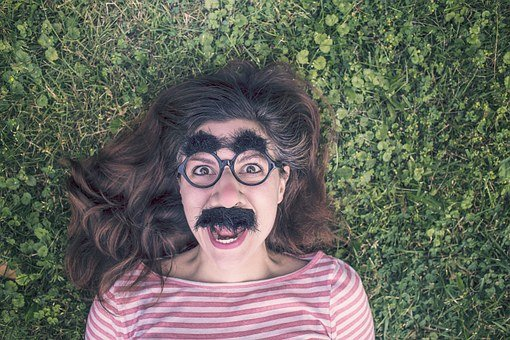 A white woman with brown hair  is lying in a field of clovers. She is wearing a mask with bushy eyebrows, glasses, a fake nose, and a fake mustache. She is screaming.