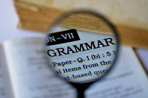 A magnifying glass showing the word GRAMMAR for the 5 things to mind on website content creation.