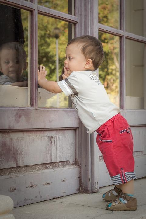 Bebê em pé, apoiando com as mãos em uma janela de vidro.