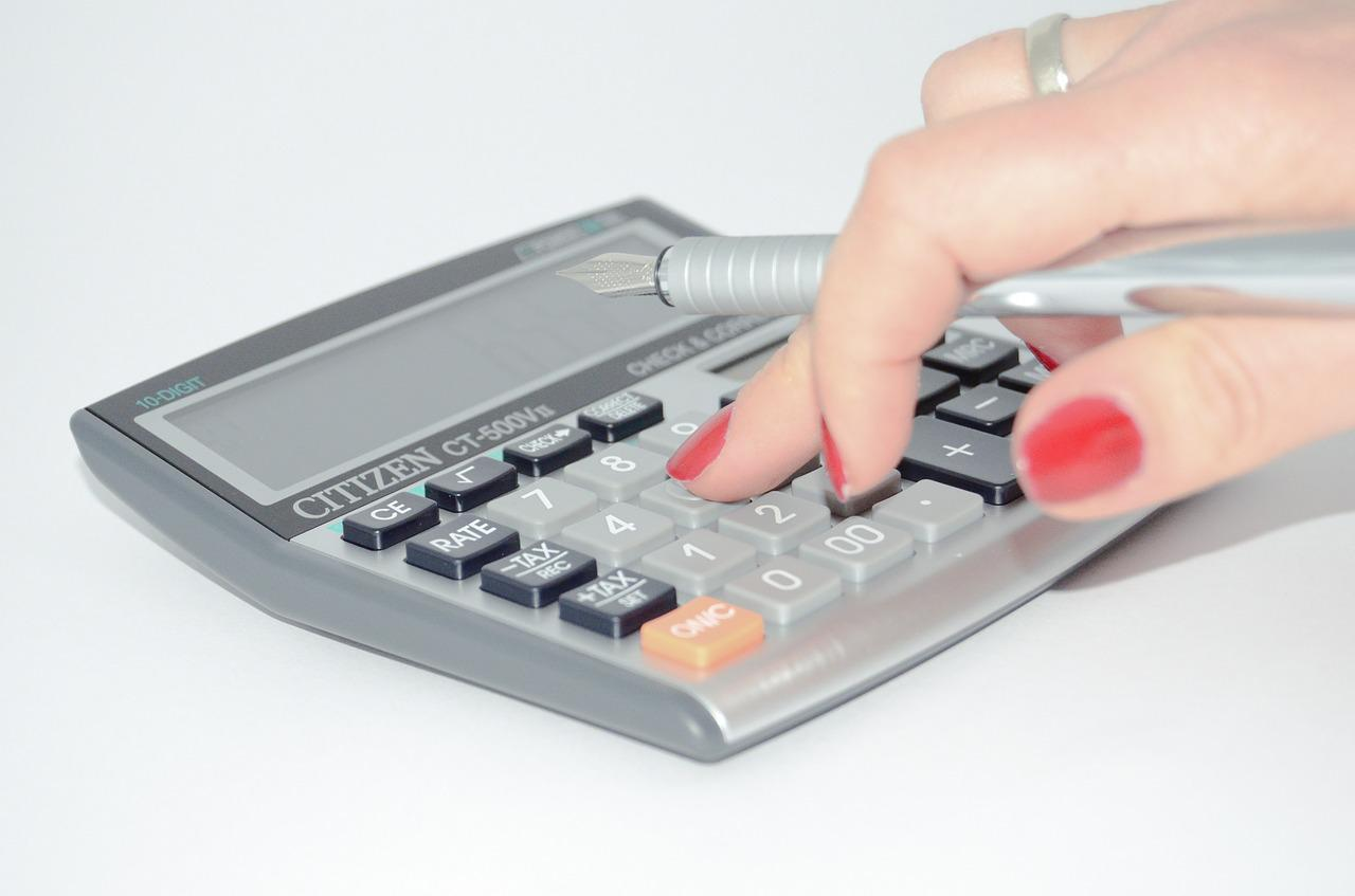 A hand presses on a key of the calculator while holding a fountain pen