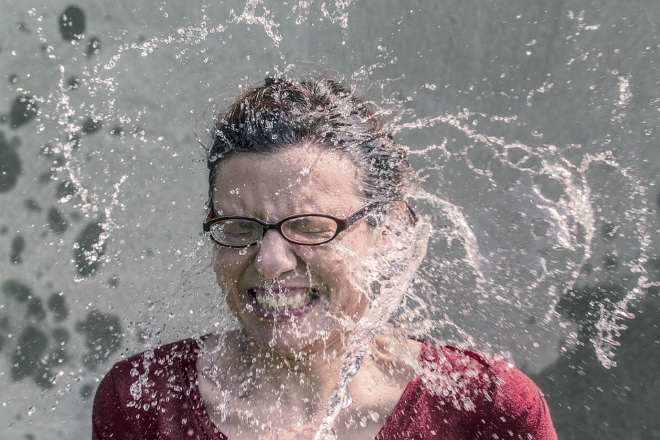 Woman get a large splash of water in the face