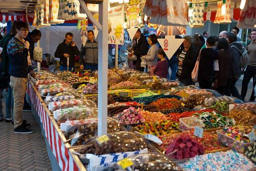 Shoppers around food products at a street market