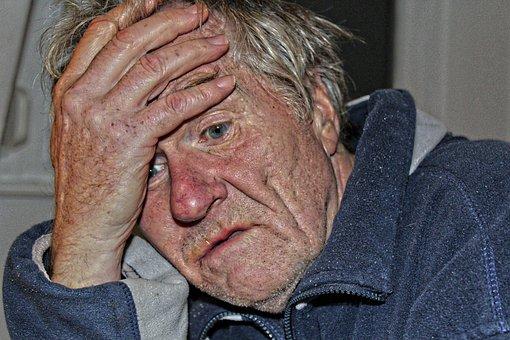 alter Mann hält sich den Kopf