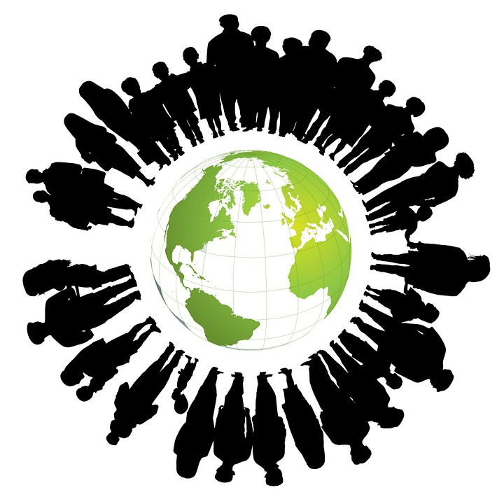 A group of silhouettes of people circled around a globe