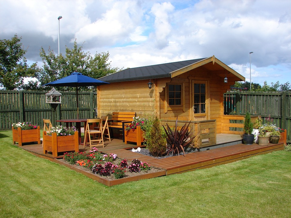 Garden shed on wooden decking surrounded by flowers