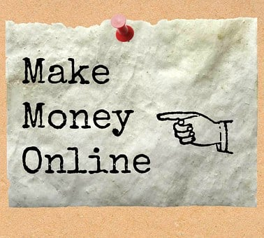 Make money online with a finger pointing to the words on a white cloth pinned to a brown board