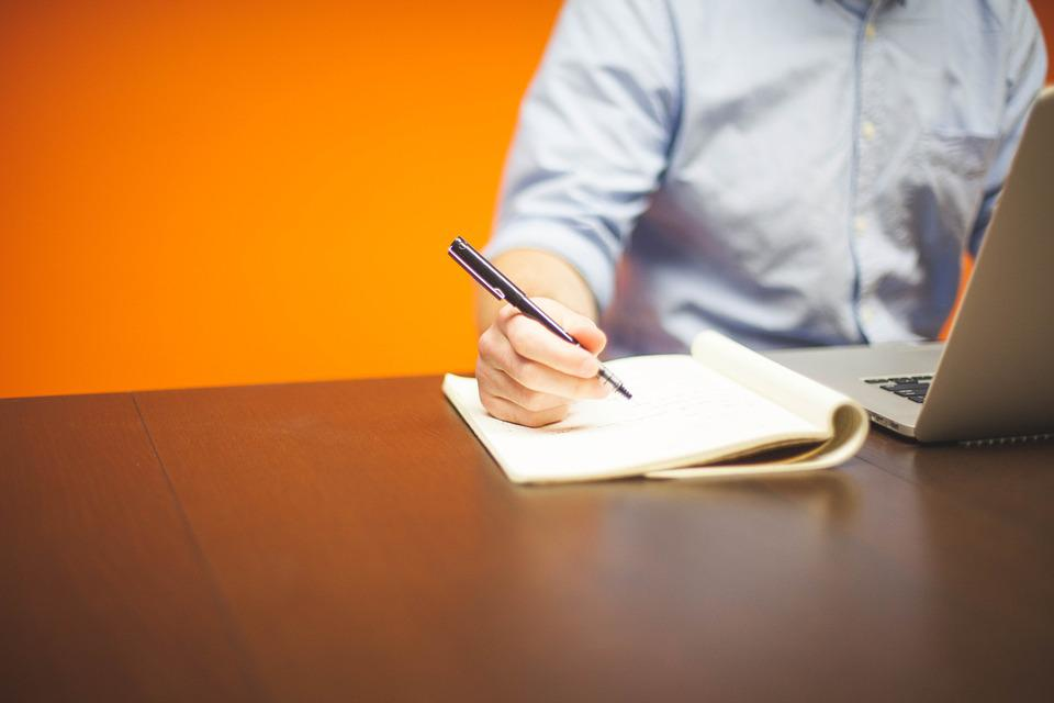 En mann skriver på papir mens han undersøker emnet på nett.