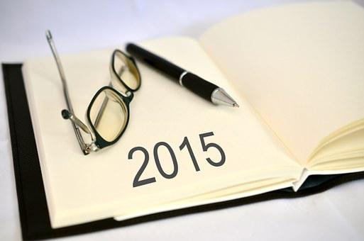 The year 2015 written in a book with glasses and a pen to signify top 100 companies for remote jobs