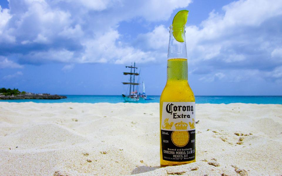 Corona Extra bottle in the sand.
