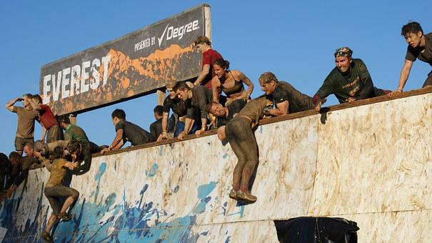 People being dragged ip a wall in tough mudder