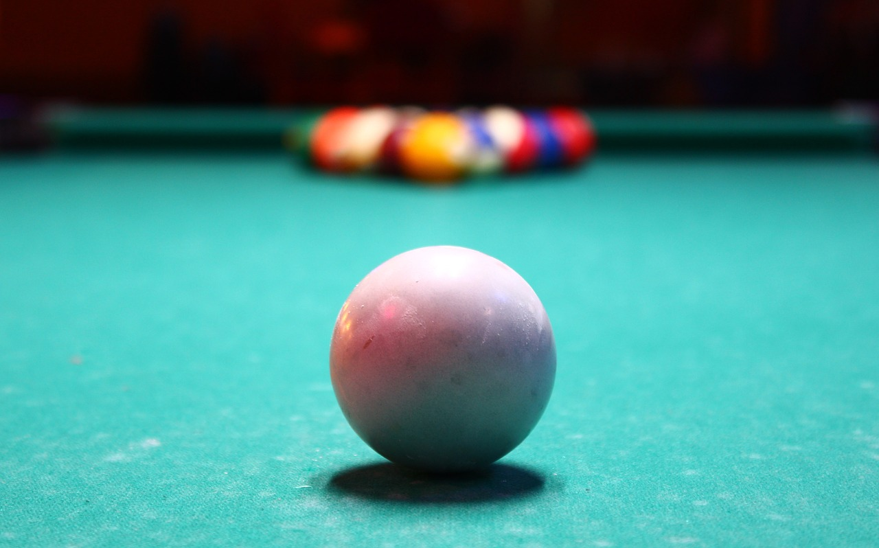 A white pool ball in the foreground with a racked group of coloured balls in the background.