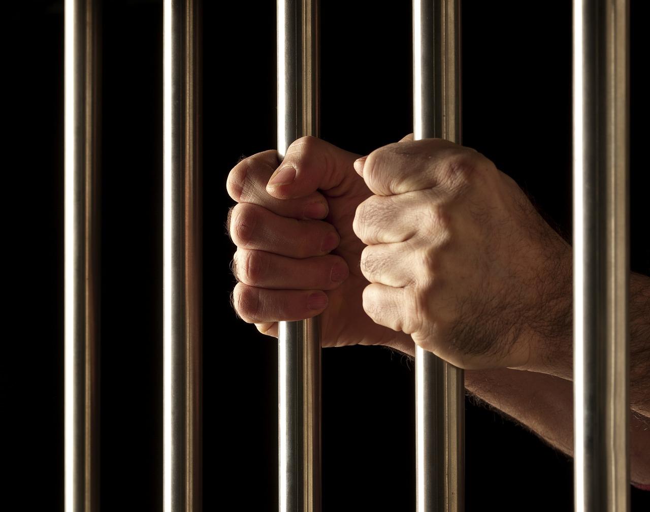 Hands grasping jail bars