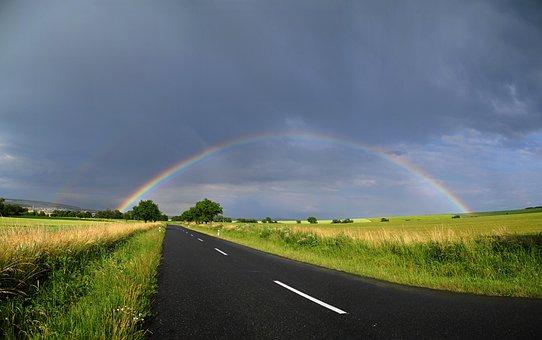道路と空にかかる虹
