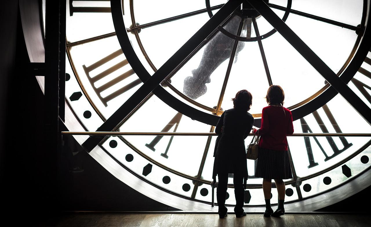 Dzieci stoją przed wielkim zegarem. Podpis: Jak języki odmierzają czas?