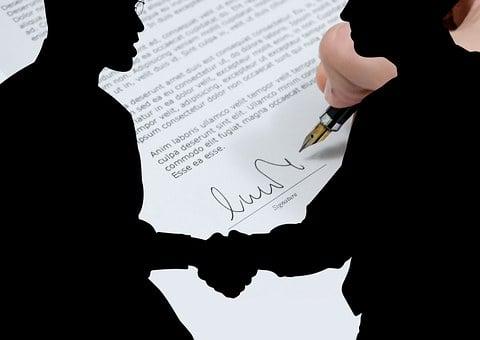 Zwei Personen geben sich die Hand, unterschreiben einen Vertrag