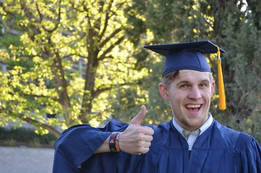 Male student in cap and gown giving a thumbs up.