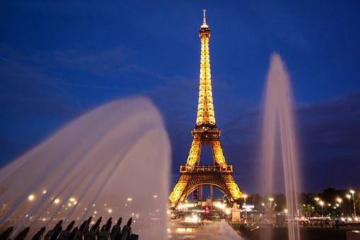 Eiffel Tour at Paris in shimmering light and water fountains