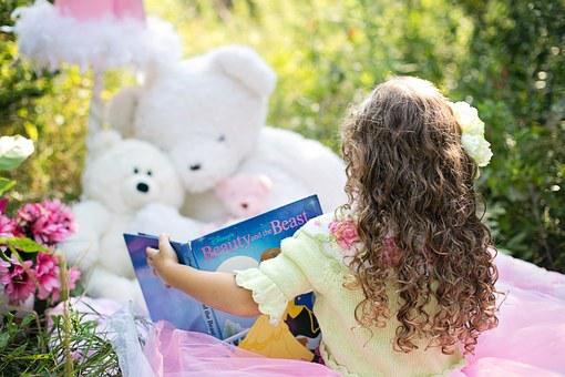 girl readinf story to her stuffed toy bears