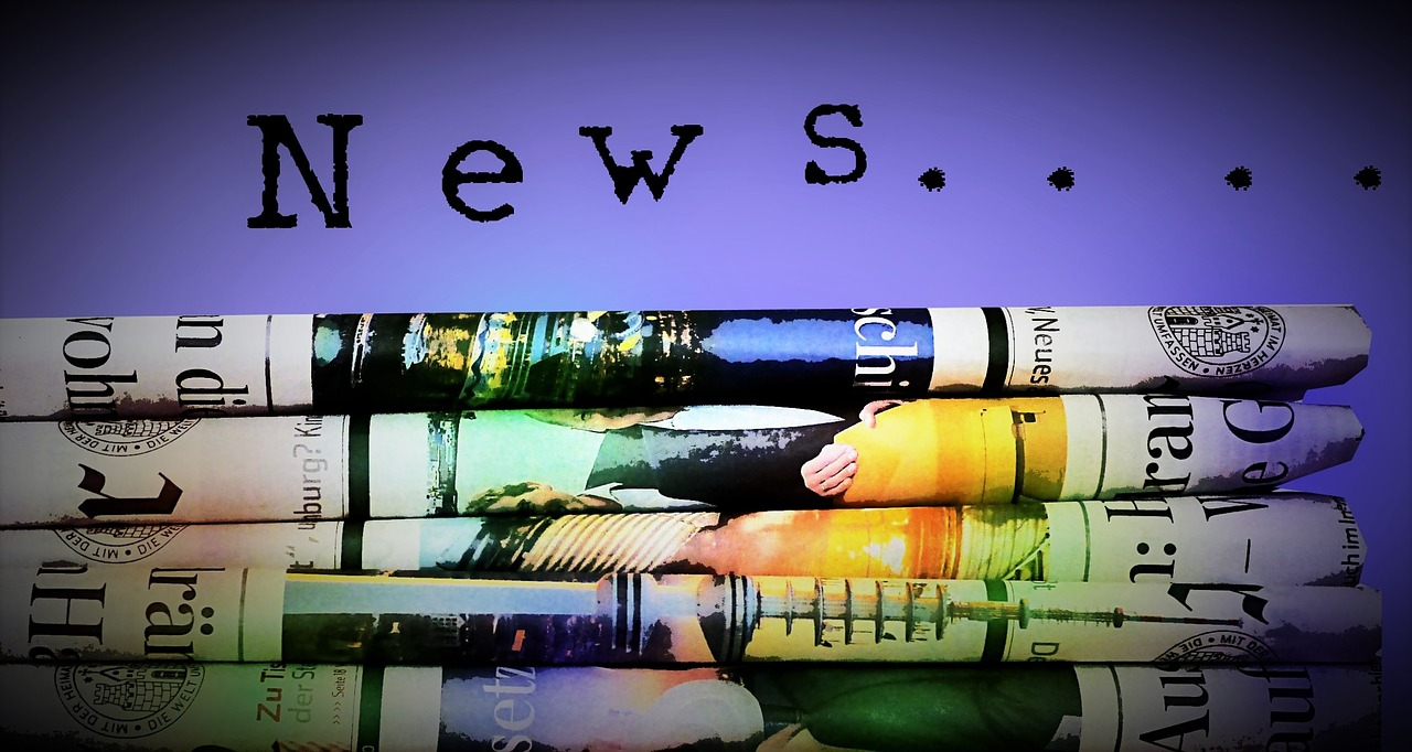 A colourful stack of newspapers are folded at the bottom of the screen. The word 'news' in typewriter font is written in black across a blue background at the top of the image.