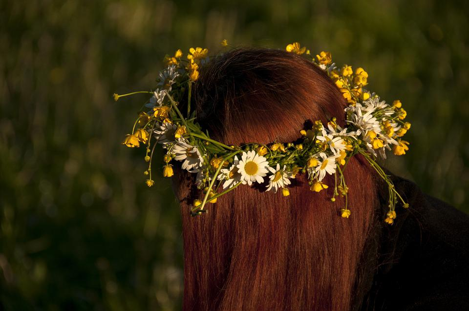 A woman's head is shown wearing a flower crown of yellow and white flowers.  Her hair is red and you do not see her face.