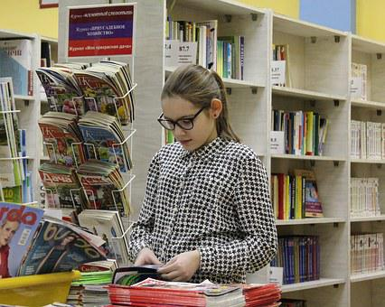 Girl standing before a book rack to signify publish in article directories