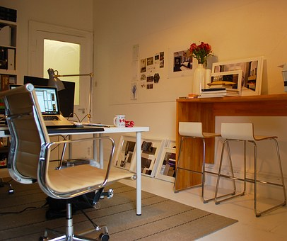 A home office showing adesk, chair, computers and working accessories