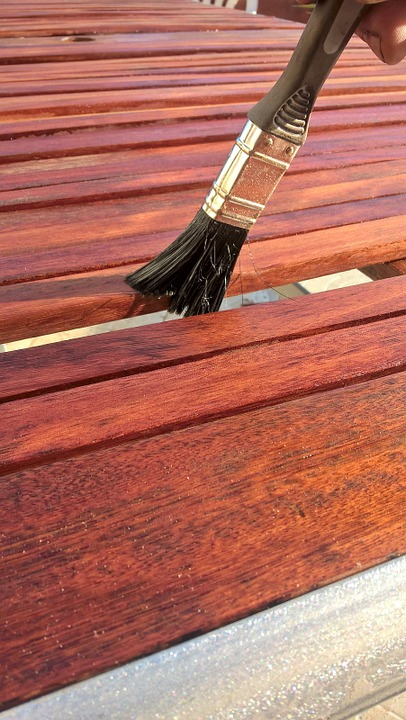 brush applying warm toned stain to wood