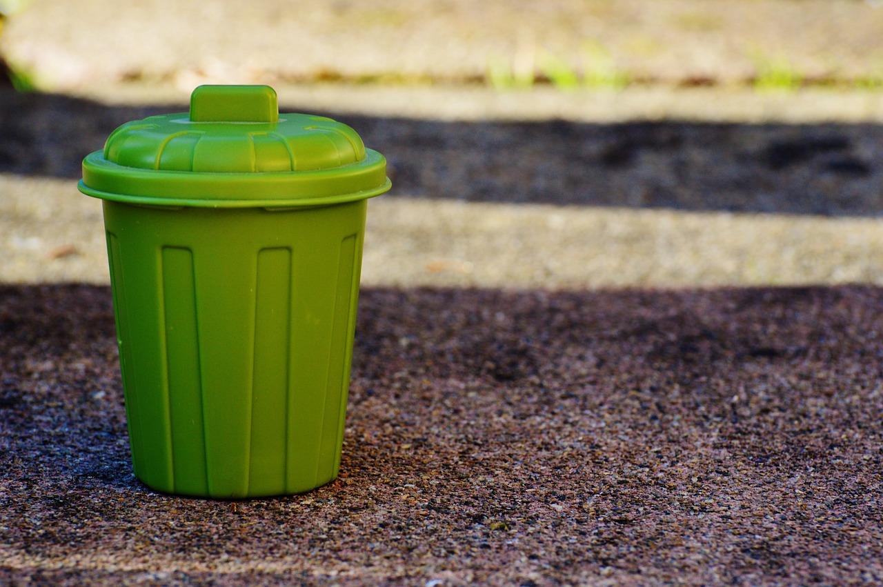 A green plastic trash bin.