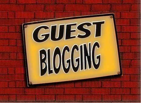 A slanting yellow triangular sign on a birck wall showing GEST BLOGGING as part of My personal experience with AWeber as an affiliate and a customer