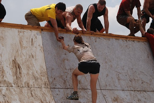 People lending a hand to a lady to scale a wall