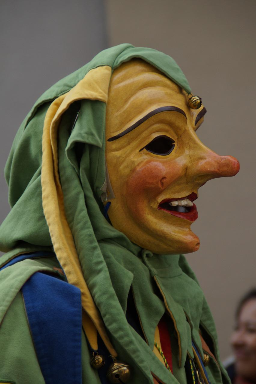 A medieval court jester wearing a mask