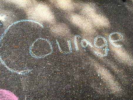 Courage written on a road surface for 301 inspirational and motivational quotes