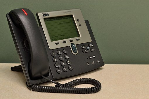 A dark-colored telephone set on a desk to signify support